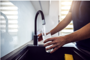 man-hand-filling-glass-of-water-from-kitchen-sink
