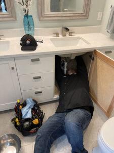 technician-fixing-plumbing-under-sink