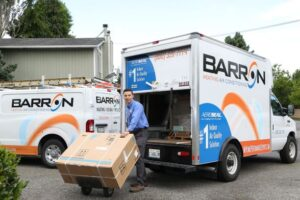 technician-with-boxed-HVAC-system-standing-in-front-of-Barron-truck