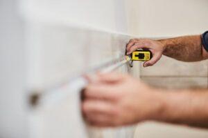 technicians-hands-using-measuring-tape